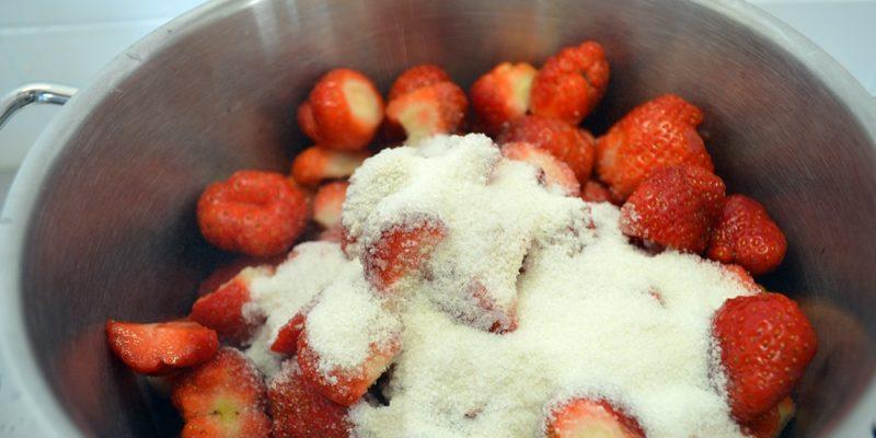 Gerüstete Erdbeeren mit Zucker in der Pfanne