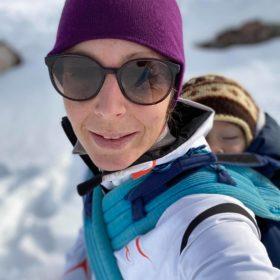 Frau mit Sonnenbrille im Winter, mit schlafendem Kind in der Rückentrage