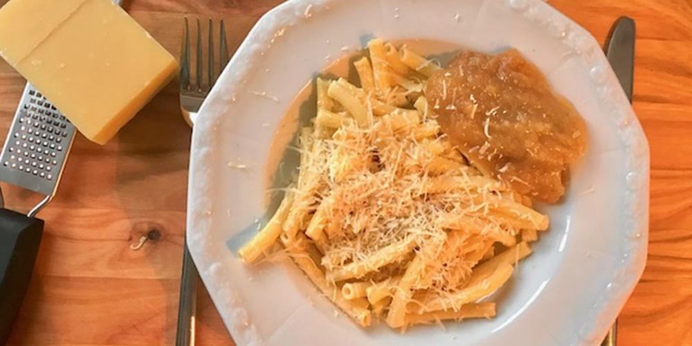 Teller mit Aelplermaccaronen und Apfelmus, dazu Käse und eine Käseraffel