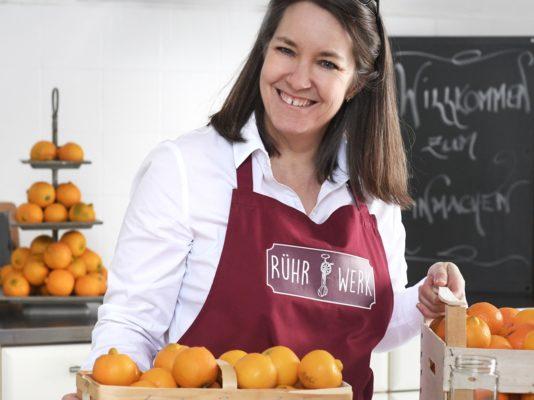 Karin Eggenberger mit Rühr-Werk Schürze und verschiedenen Zitrusfrüchten in der Rühr-Werk Küche.