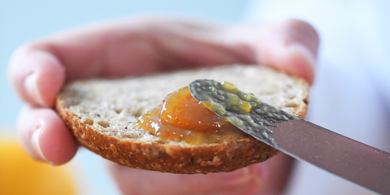 Brot wird mit Blondorangen Marmelade bestrichen