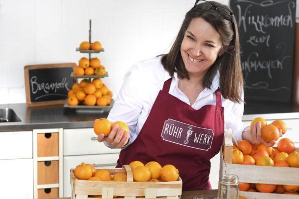 Karin Eggenberger alias Frau Rührwerk in der Küche. Auf dem Tisch verschiedene Zitrusfrüchte.