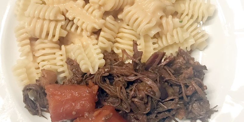 Angerichteter Teller mit Pulled Beef, geschmorten Karotten und Radiatorenudeln.