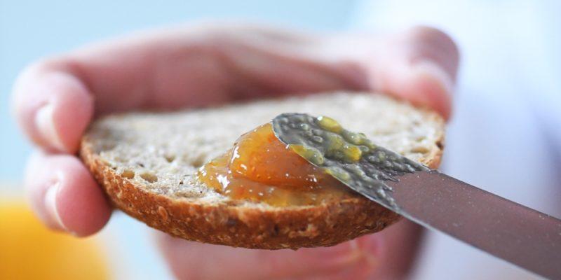 Brot wird mit Marmelade bestrichen