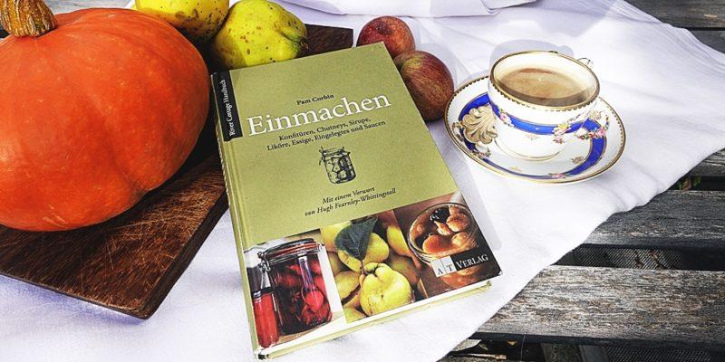 Buch mit einem Kaffee, Kürbis, Quitten auf weissem Tischtuch fotographiert